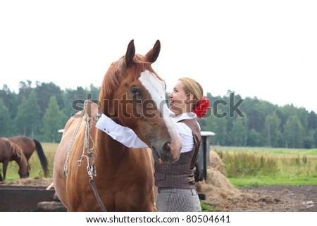 Young beautiful blonde woman putting on a headcollar on  chestnut danish warmblood horse