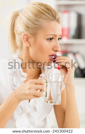 Young beautiful blonde woman takes a pill in the workplace, in the background you can see the shelves with binders. - stock photo
