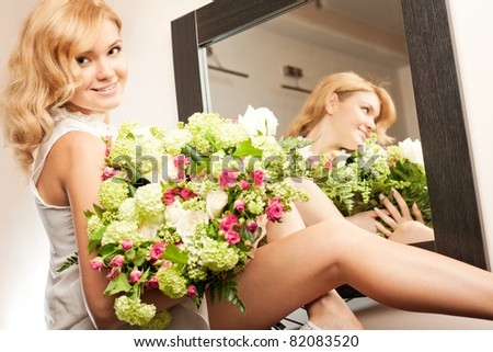 Young beautiful blonde woman with bunch of flowers - stock photo