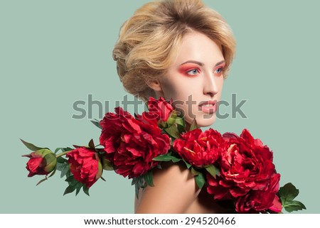 young beautiful blonde woman with red makeup and flowers on green background. studio shot. side looking. Developed from RAW, edited with special care and attention - stock photo