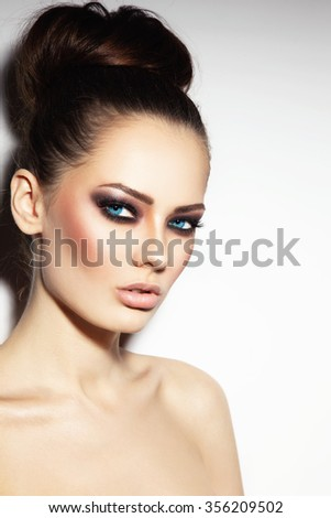 Young beautiful blue-eyed woman with smoky eyes and stylish hair bun - stock photo