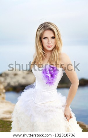 young beautiful bride in wedding dress at the beach at sunset spring summer day. Sexy romantic woman at sea shore - stock photo