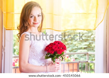 Young beautiful bride in wedding dress with red rose bouquet. Marriage and wedding concept image.