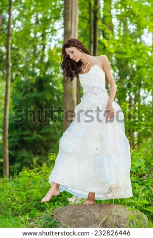 Young beautiful bride in white wedding dress with bare feet standing on bridge over stream in summer park. - stock photo