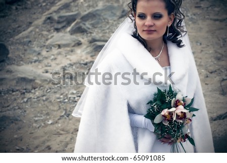 Young beautiful bride standing alone on dust near river