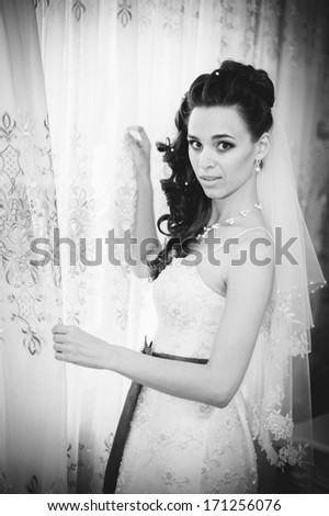 Young beautiful bride waits for groom near the window. Beautiful Bride lit by sunlight from a window. beautiful young bride standing beside a large window waiting