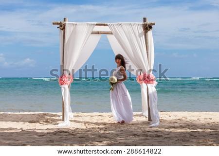Young beautiful bride wih flowers in gazebo - stock photo