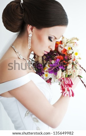 Young beautiful bride with colorful bouquet - stock photo
