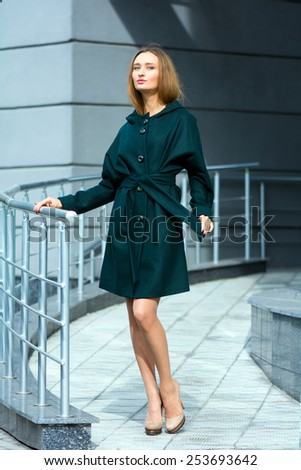Young beautiful brown-haired woman in a trendy dark green coat on gray wall background - stock photo