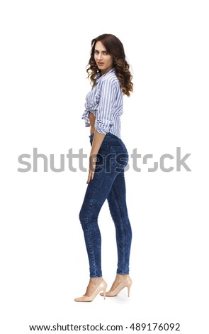 Young beautiful brown haired woman in blue jeans and pink shirt, isolated on white