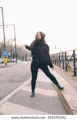 Young beautiful brunette caucasian girl dancing in the street. - freedom. dance concepts - stock photo