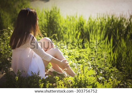 Young beautiful brunette caucasian girl in white dress sitting on a grass with her back to us, looking in front of her. summer day, outdoors. lifestyle. leisure. copy space - stock photo