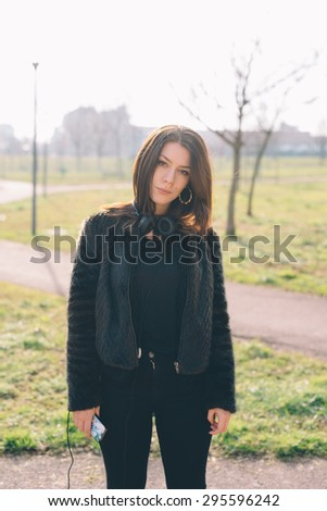 Young beautiful brunette caucasian girl listening to music in a city park - stock photo