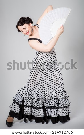 young beautiful brunette female spanish flamenco dancer in black and white flamenco dress dancing with white fan in studio on gray background - stock photo