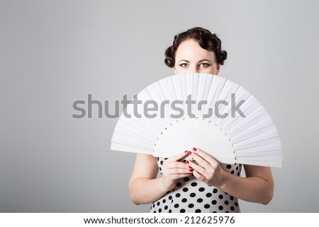 young beautiful brunette female spanish flamenco dancer in black and white flamenco dress posing with white fan in studio on gray background - stock photo
