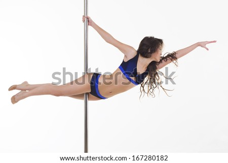Young beautiful brunette girl doing pole dancing exercise