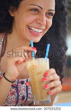 Young beautiful brunette girl drinking iced coffee and having fun. - stock photo