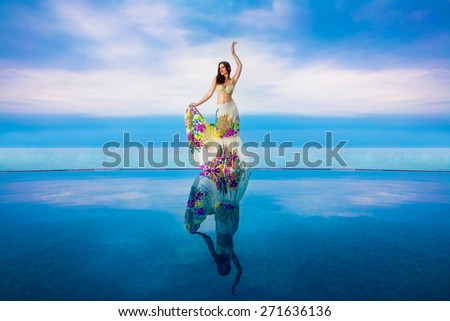 Young beautiful brunette girl in a white swimsuit with a waving skirt is next to the infinity pool. Tropical sea in the background. Summer vacation. - stock photo