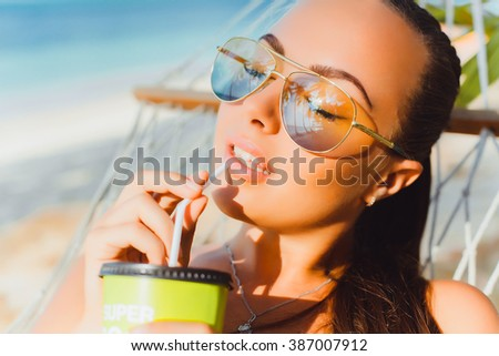 young beautiful brunette girl in sunglasses and yellow bikini tanned skin,drinking morning fresh smoothie, fruit juice,cocktail fashion outdoor, close up, cute,pretty woman - stock photo