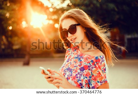 young beautiful brunette girl in sunglasses holding a smart phone, messages, posting photos to instagram, checks email,writes to friends SMS, outdoor portrait, close up, posing on the street at sunset - stock photo