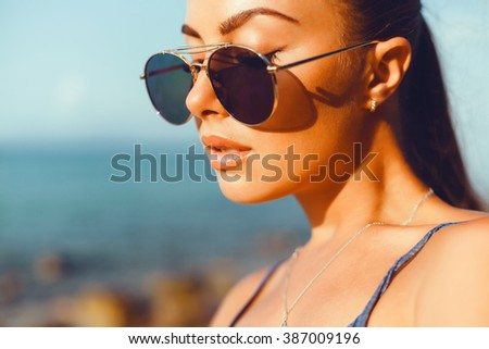 young beautiful brunette girl in sunglasses with beautiful skin and lips, posing on the beach, fashion portrait, fashion outdoor, close up, cute, miami beach, pretty woman - stock photo
