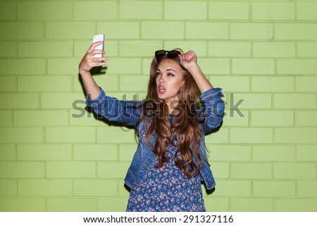 young beautiful brunette girl with yellow shortboard penny skateboard taking a selfie self portrait of herself coquettishly posing with her sunglasses at the camera on her smartphone digital camera  - stock photo