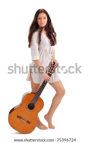 Young beautiful brunette lady in white chemise with acoustic guitar