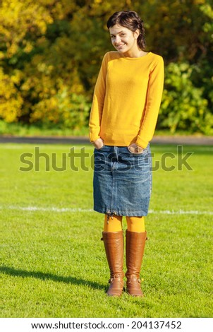 Young beautiful brunette laughs against autumn wood. - stock photo