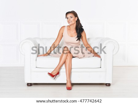 Young beautiful brunette posing in a beige dress sitting on white sofa