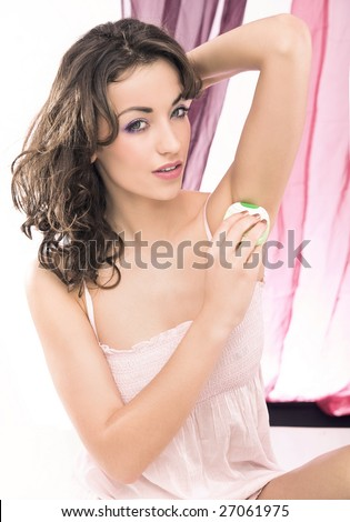 Young beautiful brunette shaving her armpit - stock photo