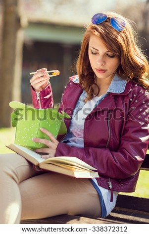 Young beautiful brunette sitting on a wooden bench in a park and eating Chinese food and reading a book