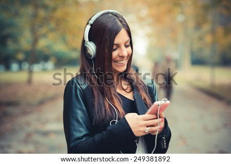 young beautiful brunette straight hair woman in the park during autumn season - listening to music with headphones and smartphone - stock photo