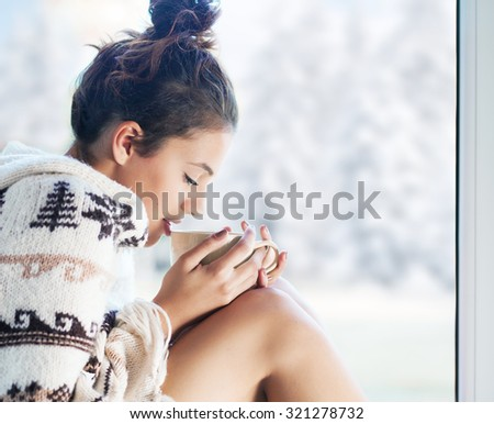 Young beautiful brunette woman drinking cup of coffee wearing knitted nordic print poncho sitting home by the window. Blurred winter snow tree background.  - stock photo
