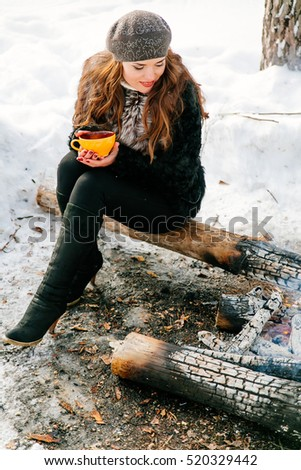 Young beautiful brunette woman holding a Cup of tea outdoors in winter sitting on a log near the fire
