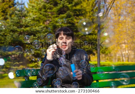 young beautiful brunette woman in a black leather jacket blowing bubbles sitting on a bench in city park - stock photo