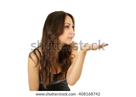Young beautiful brunette woman in black dress blowing on hand on white background - stock photo