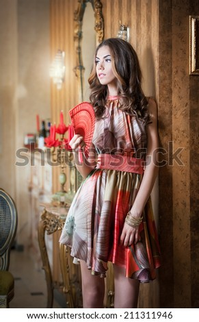 Young beautiful brunette woman in elegant multicolored dress standing near a large wall mirror. Sensual romantic lady holding a red fan in luxurious vintage interior, daydreaming. Pretty girl with fan - stock photo