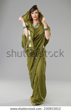 Young beautiful brunette woman in indian green dress - stock photo