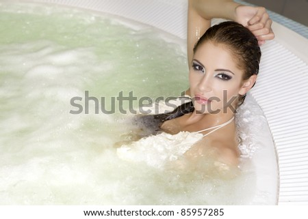 Young beautiful brunette woman in jacuzzi