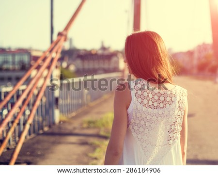 Young beautiful brunette woman posing in sunset in city - stock photo
