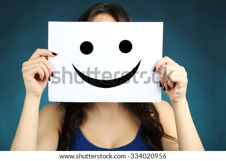 Young beautiful brunette woman showing a happy emoticon on blue background