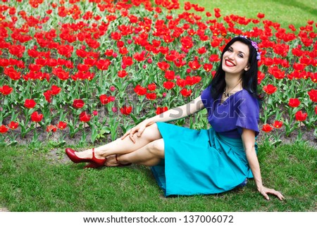 Young beautiful brunette woman smiling and sitting on grass against landscape with tulips - stock photo