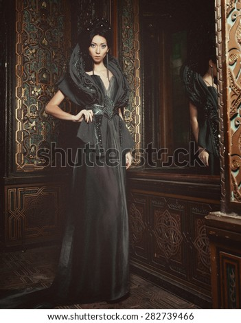 Young beautiful brunette woman standing in the palace room - stock photo