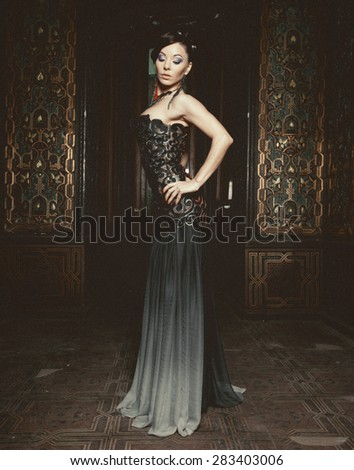 Young beautiful brunette woman standing in the palace room