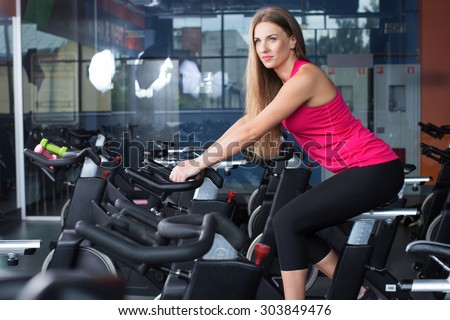 Young beautiful brunette woman, wearing in sportswear, energetically riding on exercise bike in gym, full body - stock photo