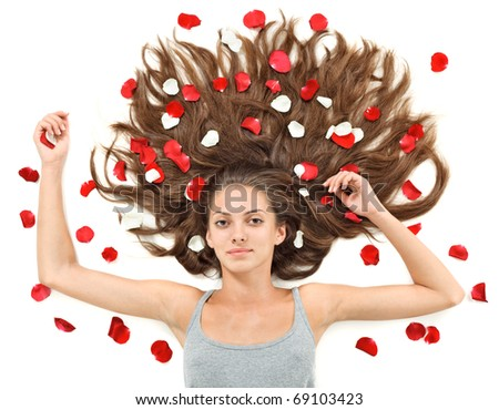 Young beautiful brunette woman with scattered long hairs and rose petals on white