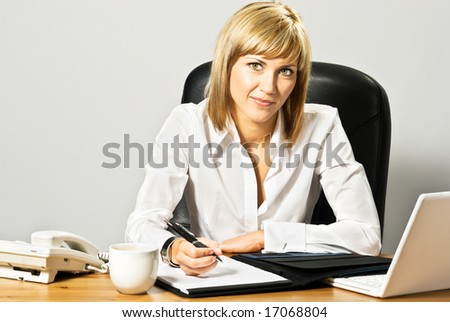 Young beautiful business lady at desk writing.
