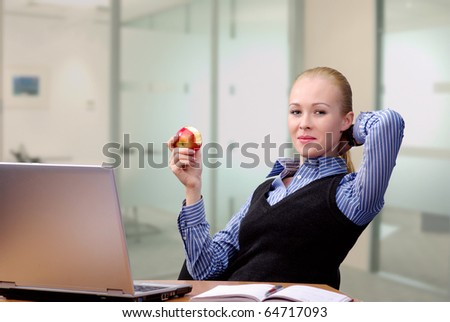 Young beautiful business lady at table resting with an apple - stock photo