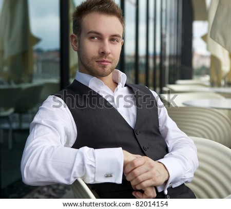 Young beautiful business men sits at a table. Outdoor photo.