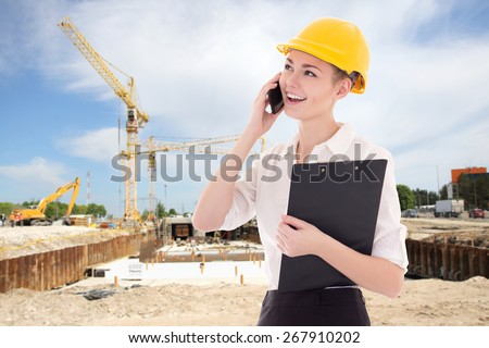 young beautiful business woman architect in builder helmet talking by phone at construction site - stock photo